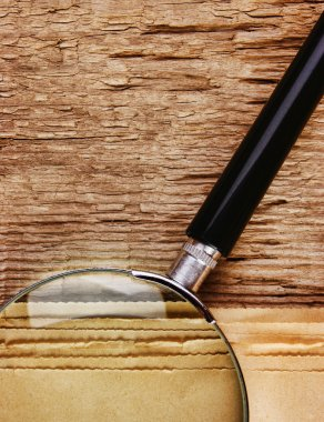 edge of the old newspaper and magnifying glass on a wooden backg
