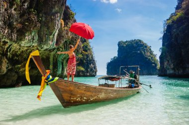 young girl standing in a wooden boat with a red umbrella in the