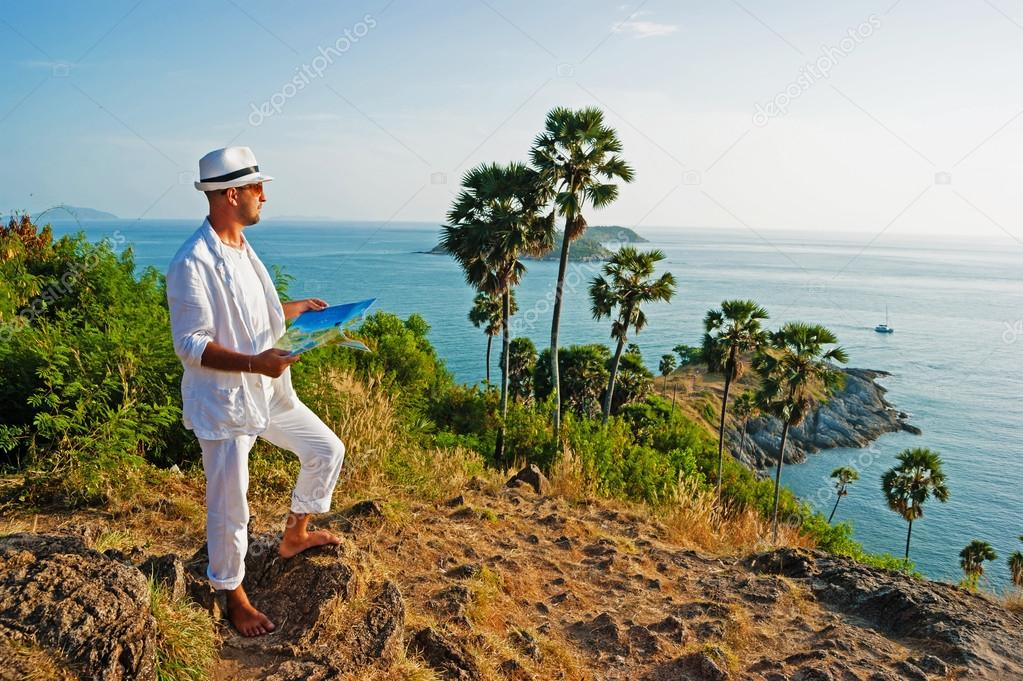 A young man in a white suit standing on sea shore with a map
