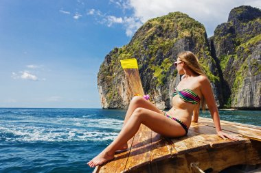 young girl in bikini sitting on boat on the beach Maya Bay Phi