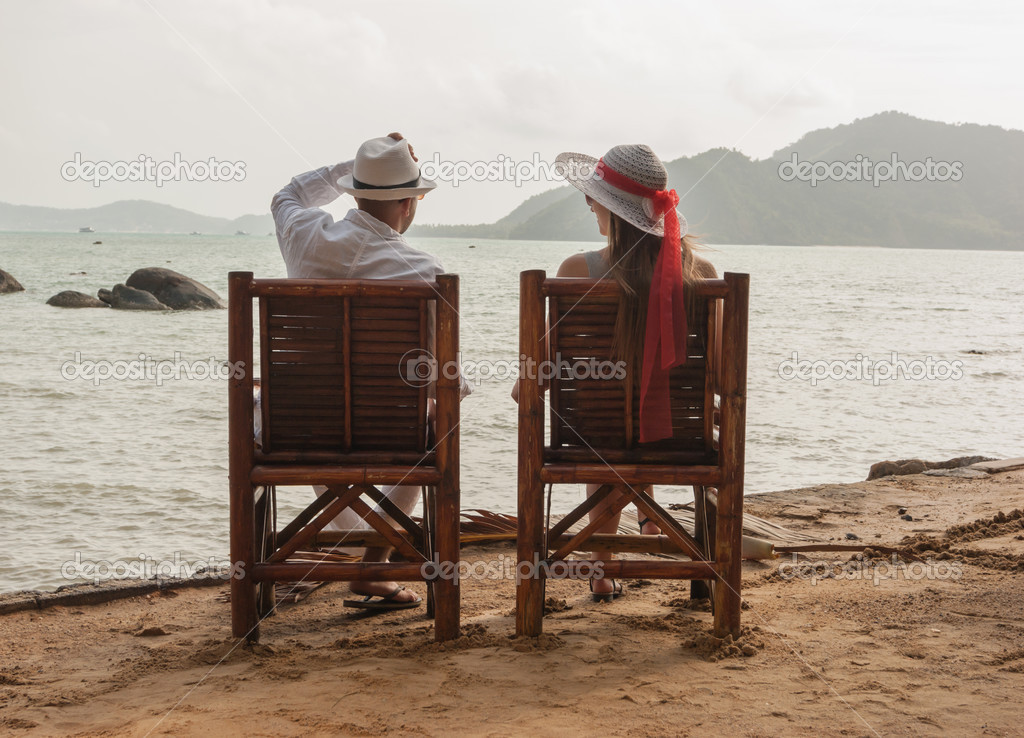 Man and a girl sitting on the beach