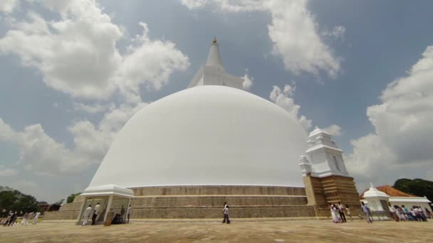ANURANHAPURA, SRI LANKA - APR 16: Pilgrims in white clothes go round huge white sacred stupa Ruwanmalisaya dagoba on Apr 16, 2013 in Anuradhapura, Sri Lanka
