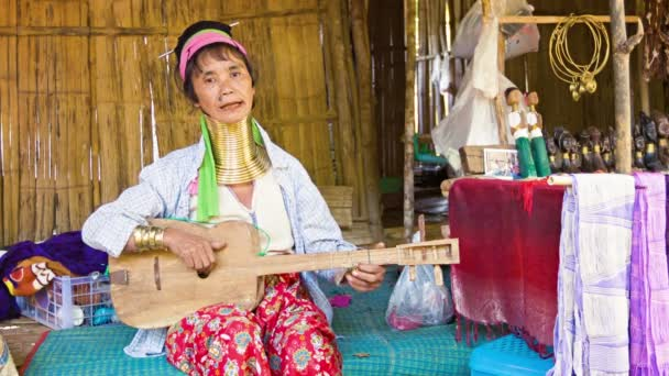 CHIAND RAI, THAILAND - 04 DEC 2013: Kayan Lahwi (Long-Necked Kayan) woman with neck rings play wooden guitar in hill tribe village.