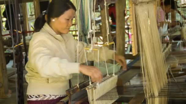 LUANG PRABANG, LAOS - 08 DEC 2013: Unidentified woman work on traditional spinning loom