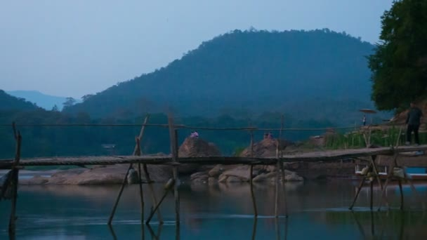 Luang prabang, laos - 08 prosinec 2013: neznámí muži projít dlouhý dřevěný most nad řekou na temný večer