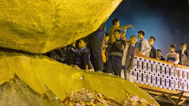 MON STATE, MYANMAR - 04 JAN 2014: Ritual gold sticking to the rock - Kyaiktiyo Pagoda. For women entry is prohibited