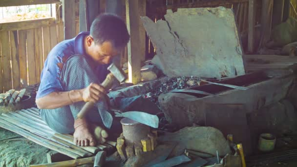 inle lake, myanmar - ca. Jan 2014: Meister arbeitet an einem großen Messer in der Schmiede