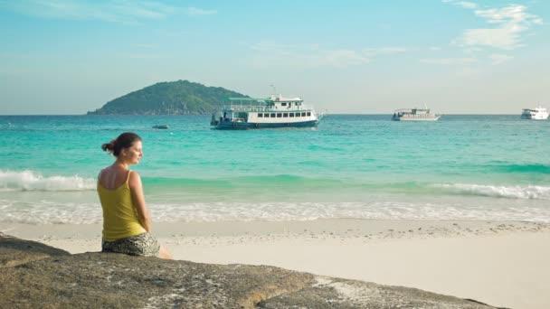 videa 1080p - mladá žena sedí na pláži a dívá se na lodě. Similanské ostrovy, Thajsko
