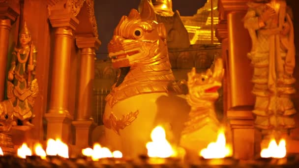 Video 1080p - Statues of mythical monsters in a Buddhist temple at night. Ritual lighting with oil lamps. Myanmar, Yangon