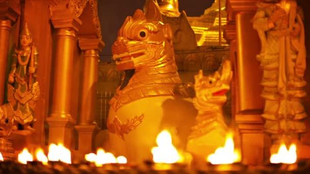 videa 1080p - sochy mytické příšery v buddhistickém chrámu v noci. rituální osvětlení s olejovými lampami. Myanmar, yangon