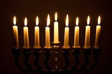 lit hanukkah menorah on black