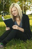 Blonďatá dívka čtení studiu na trávě