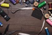 Fotografia bottoni di fili e aghi sopra il tavolo in legno marrone