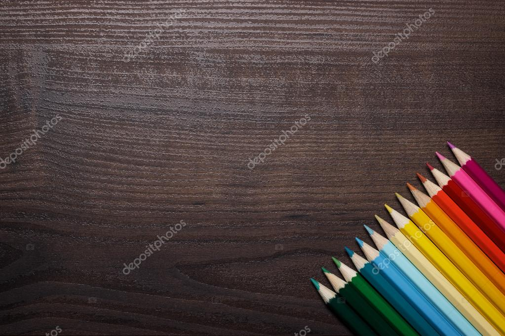Colorful pencils over brown table background