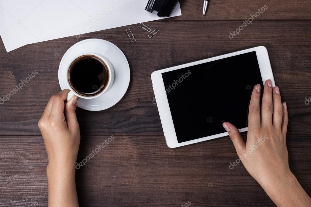 Women hands with tablet computer and coffee on table