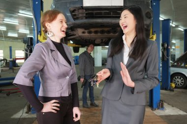 Two girls in  car service center