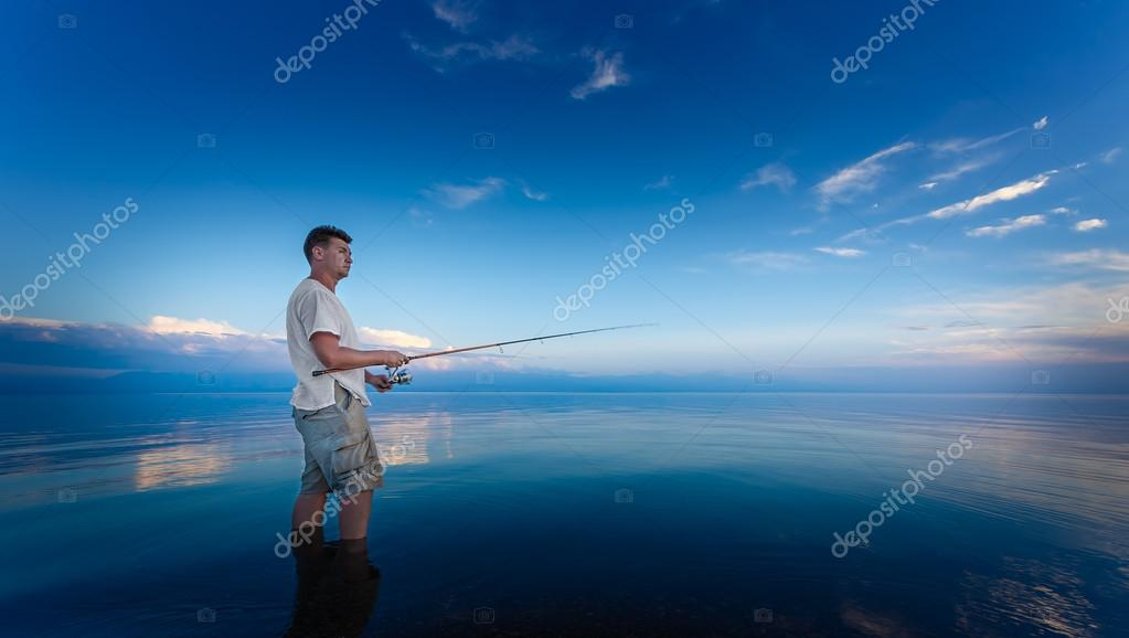 Fisher man with fishing rod silhouette on the beach at sunset