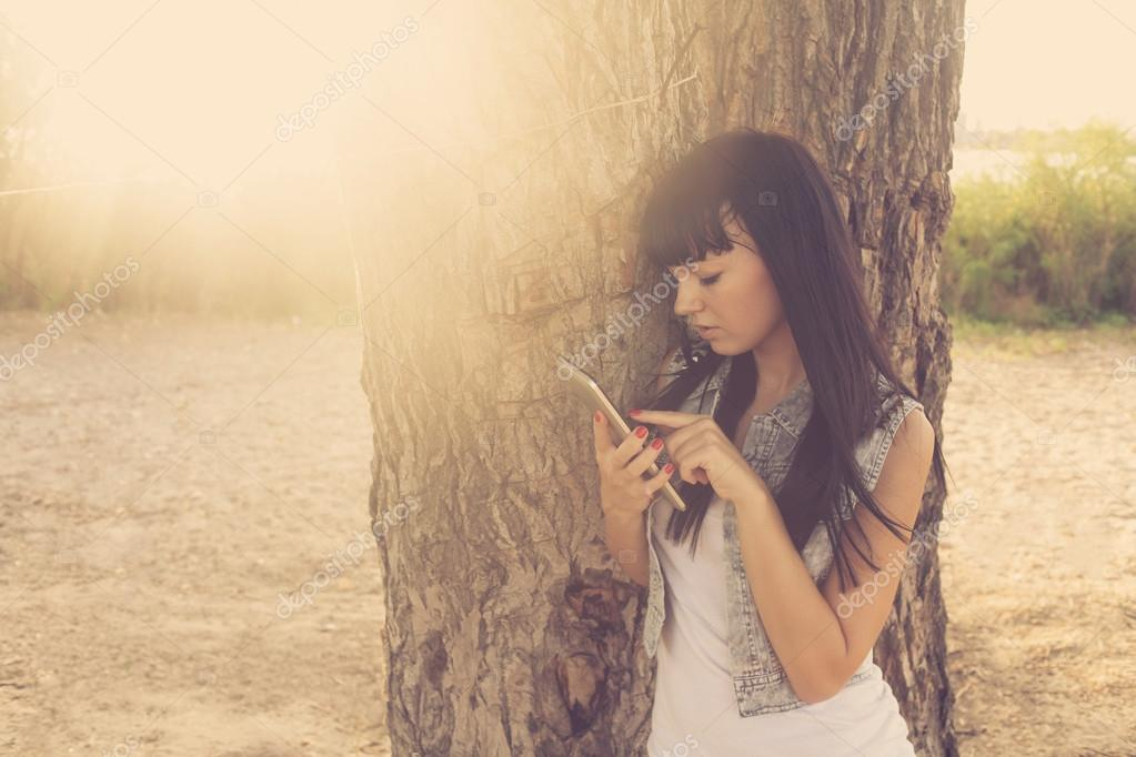 Brunette using tablet computer near tree