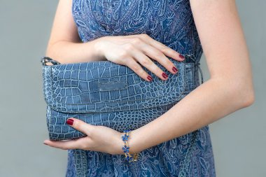 Blue closed clutch in womens hands