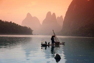 Chinese man fishing with cormorants birds, Yangshuo, Guangxi reg