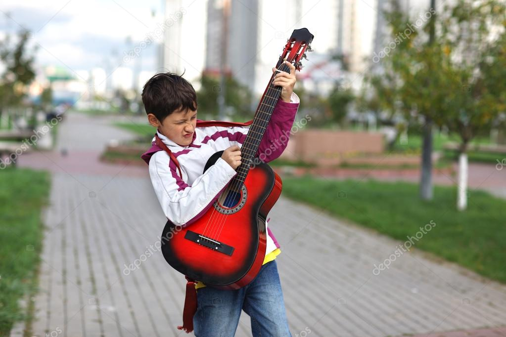 Boy playing the guitar outdoors