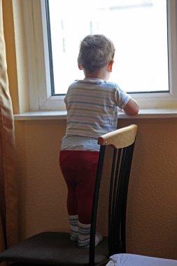 alone little boy looking in window