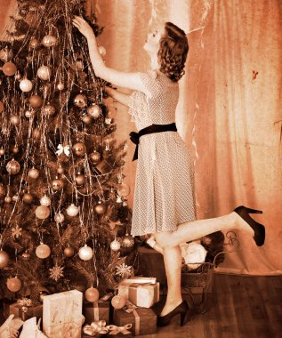 Woman dressing Christmas tree.
