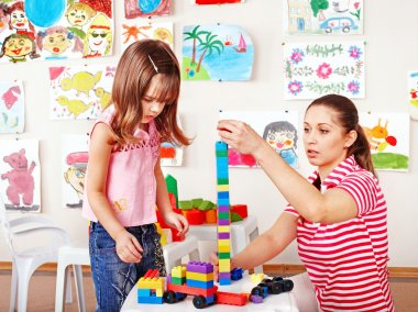 Child playing construction set with mother.