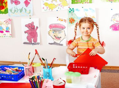 Child with scissors cut paper in playroom.