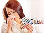 Frau mit Taschentuch mit Tabletten und Pillen