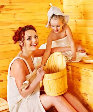Family with child relaxing at sauna.