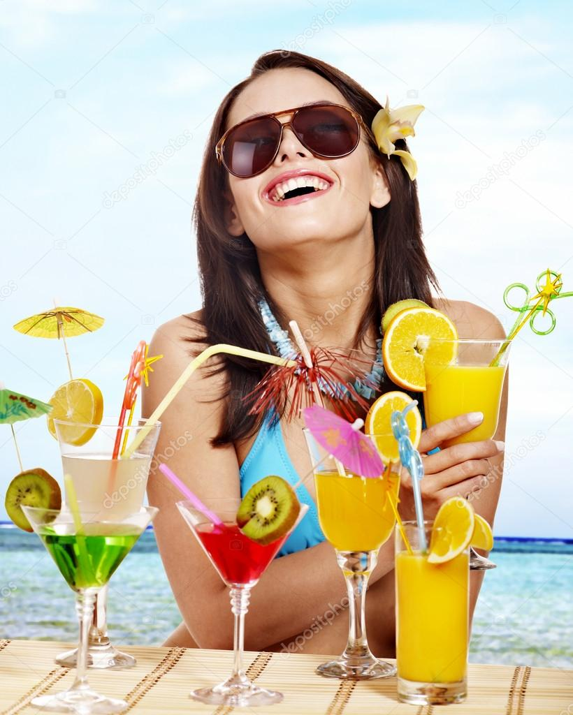 girl in bikini on beach drinking cocktail stock photo