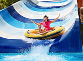 Child with mother on water slide at aquapark.
