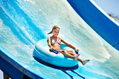 Child on water slide at aquapark.
