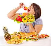 Fotografie Frau Wahl zwischen Obst und hamburger