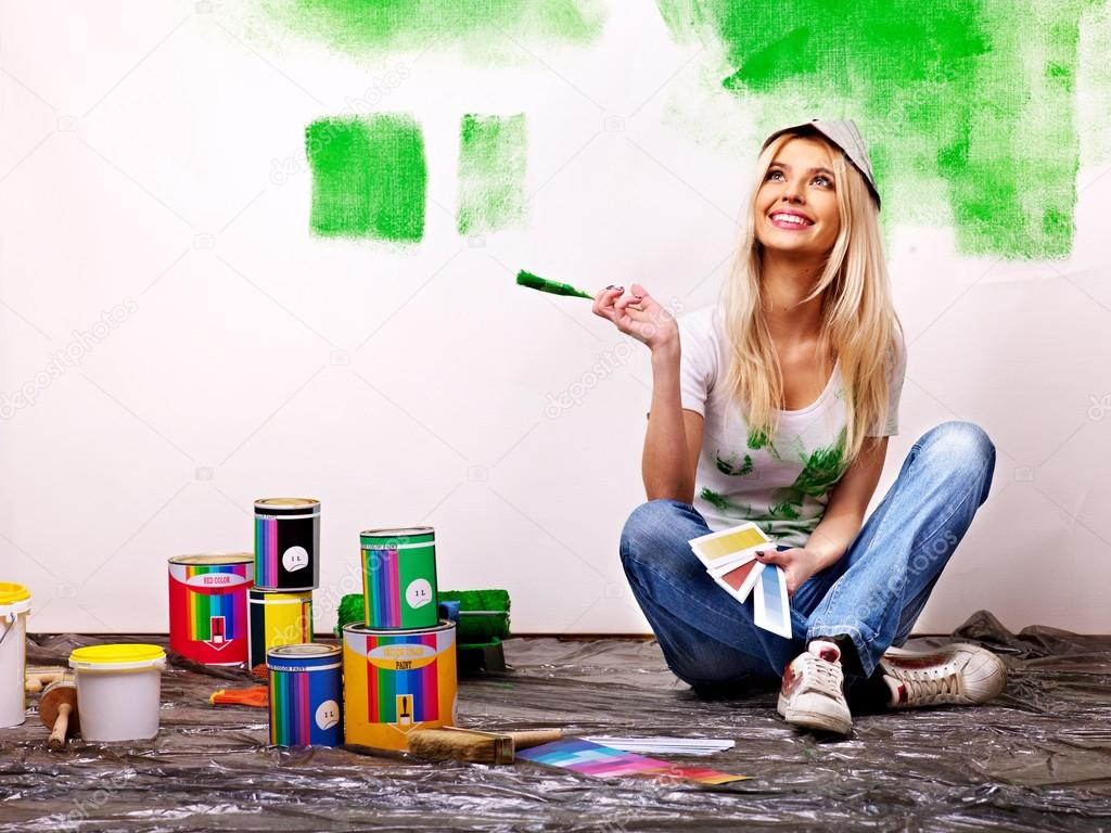 Woman paint wall at home.