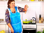 Reife Frau bereitet sich in der Küche vor.
