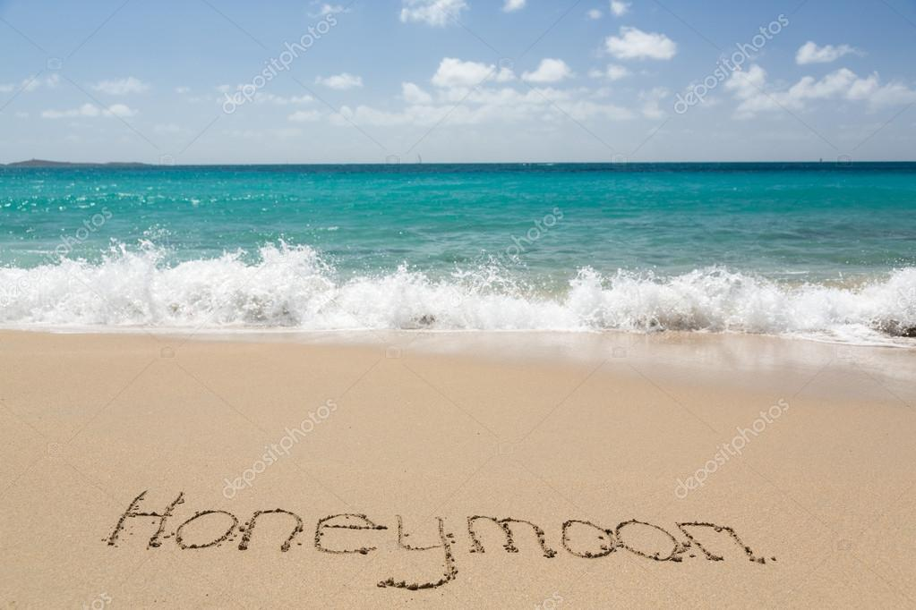 Honeymoon written in sand with sea surf