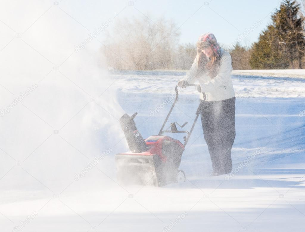 Young woman clearing drive with snowblower