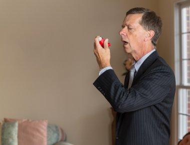 Senior businessman with asthma inhaler