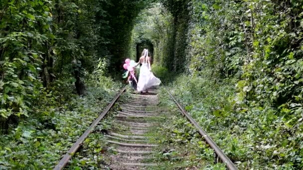 Girl walking along the forest railway.