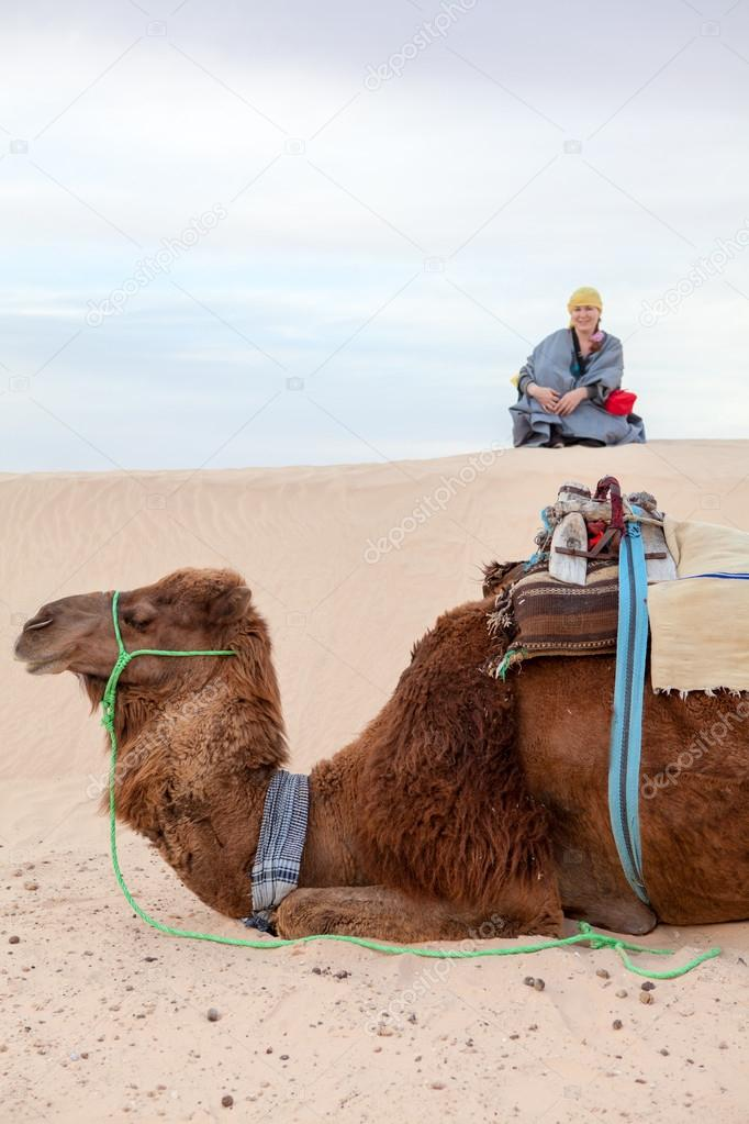 Caucasian woman sitting on sand dune in desert with camel on foreground