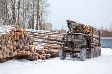 Log loader track with timber in lumber mill in winter season