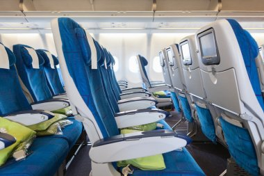Comfortable seats in cabin of huge aircraft with screens in chairs back