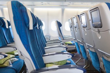 Empty comfortable seats in cabin of huge aircraft with screens in chairs back