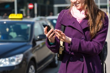 Young Woman Talking on Mobile waiting for Taxi