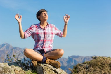Young Woman Relaxing on Top of Mountain