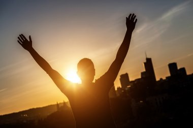 Successful Man with Raised Arms at Sunset