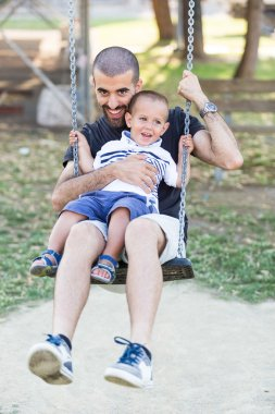 Little Boy Playing on the Swing with Father or Uncle