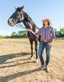 Fotografie Cowgirl mit einem schwarzen Hengst Pferd